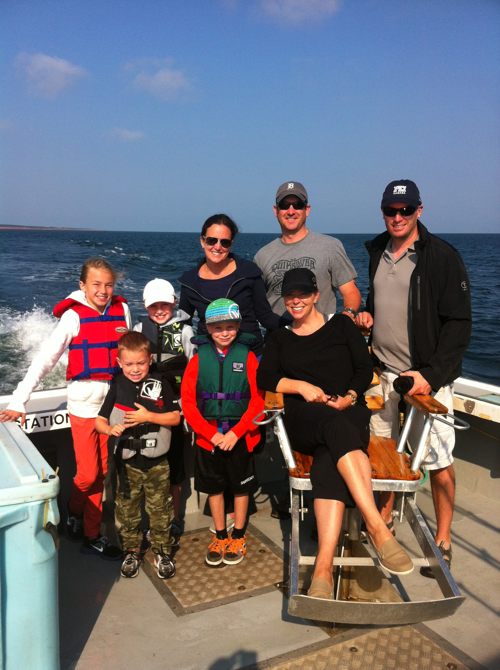 Family on deep sea charter fishing tour sitting around chair